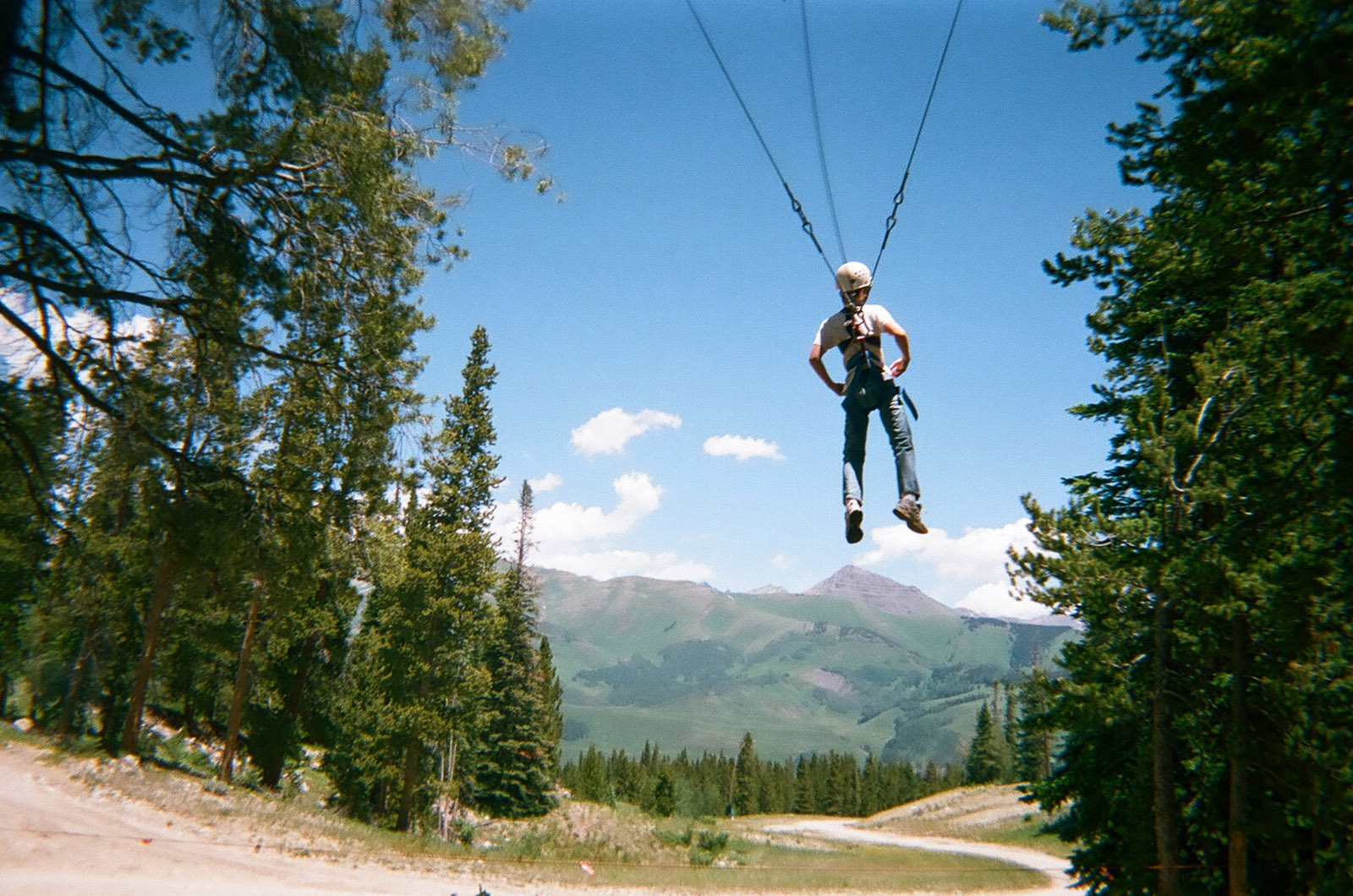 a student zip-lines in the Colorado Rockies